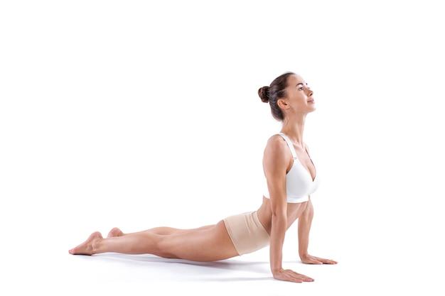 Женщина, практикующая йогу. красивая девушка практикует асаны кобры, изолированные на белом. спокойствие и расслабление.