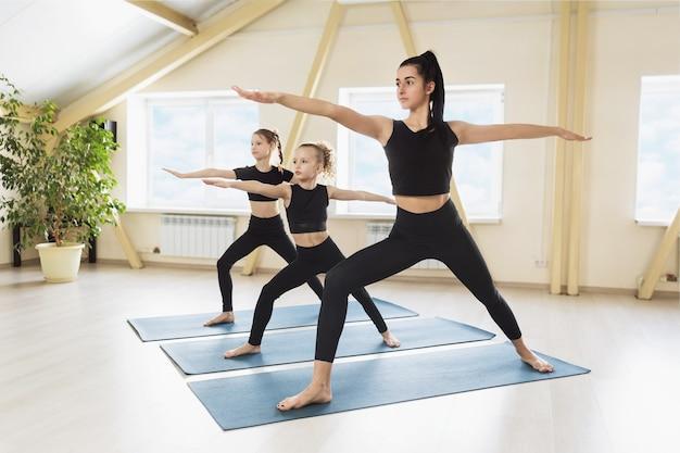 Virabhadrasana 운동 전사 포즈의 올바른 실행을 보여주는 두 학생과 함께 훈련 세션을 실시하는 요가 연습 여자