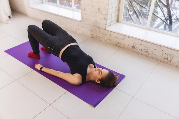 Woman practicing yoga doing ardha chakrasana pose