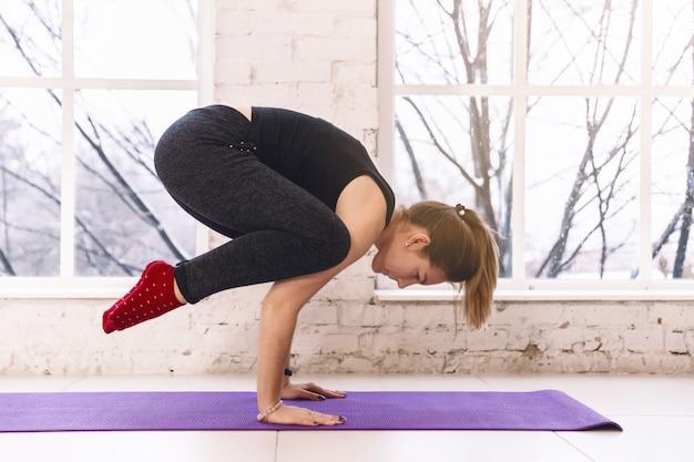 Woman practicing yoga doing bakasana hand standing balance  pose  in the light room on yoga mat indoors.