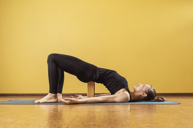 Женщина, практикующая йогу, делает позу полумоста двипада питхасана с деревянным блоком под поясницей, тренируется на коврике в студии у стены