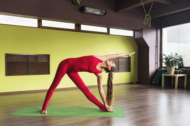 A woman practicing yoga doing the exercise utthita trikonasana an extended triangle pose
