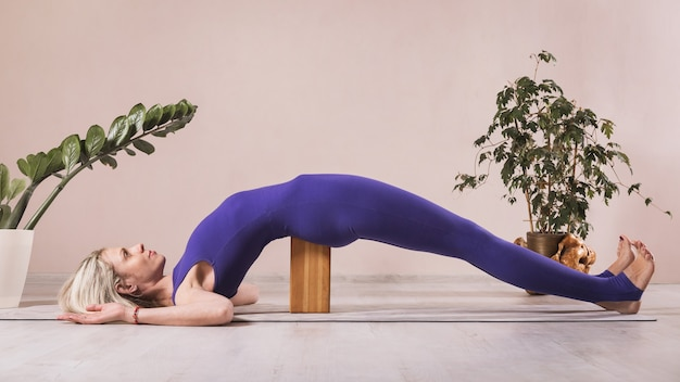 Woman practicing yoga doing seto bandha sarvangasana exercise with wooden yoga block exercising on a mat in the studio near the wall