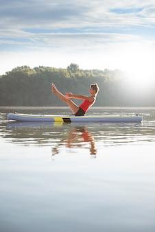 Женщина практикует йогу во время восхода солнца в лопаточной доске
