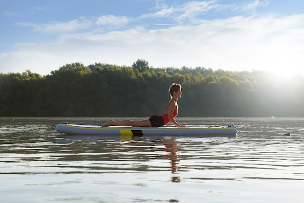 Woman practicing yoga during sunrise in paddle board