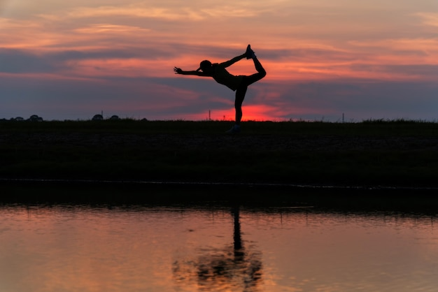 Woman practicing yoga during surrealistic sunset at the seaside. healthy concept and workout. silhouette asian woman exercise yoga pose at twilight sunset time with reflection on river.