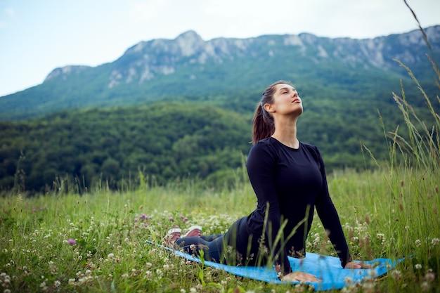 산에서 요가 운동을 하는 여자