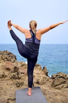 Woman practicing yoga in front of the sea