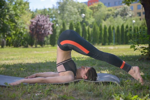 Женщина занимается йогой в парке по утрам