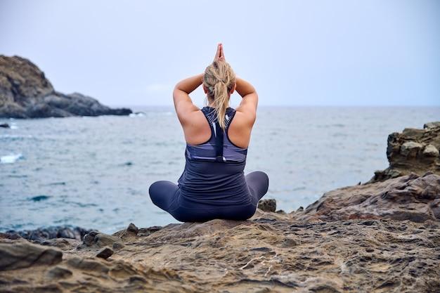 바다 앞에서 요가를 연습하는 여자