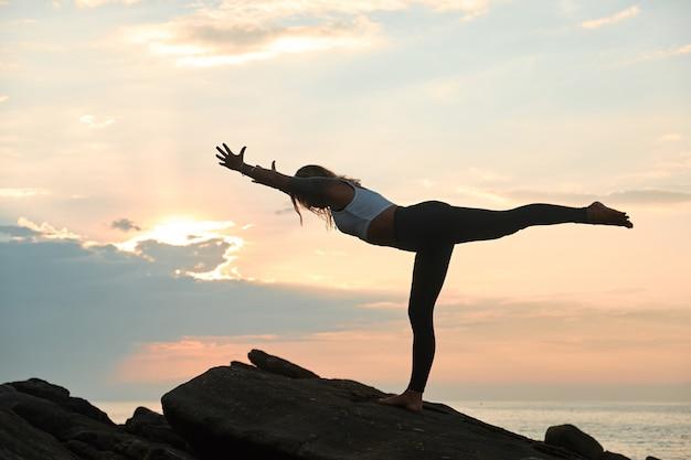 Женщина, практикующая йогу на природе