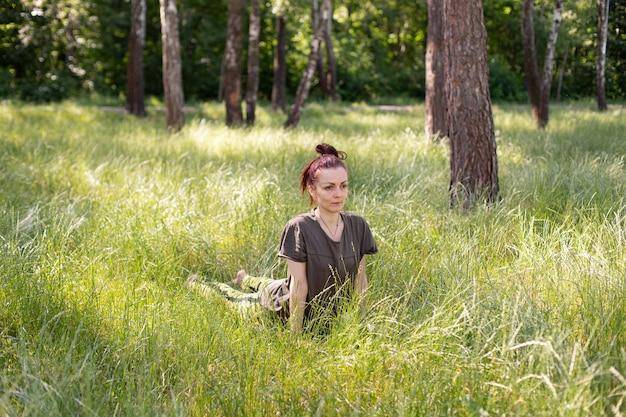 키 큰 잔디 사이 공원에서 요가를 연습하는 여자