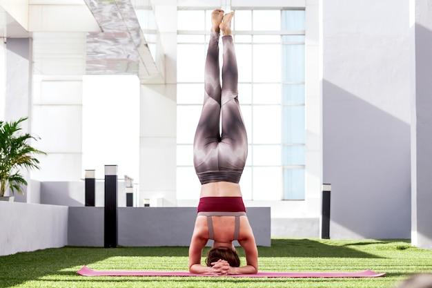 Женщина, практикующая йогу в парке - здоровый образ жизни