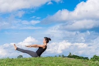 Woman practicing yoga in the park on the green grass with beautiful blue sky background