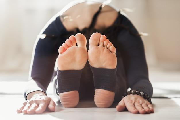 頭から膝まで座って前かがみになってヨガを練習している女性がpaschimottanasanaポーズを練習します