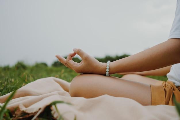 Женщина практикует урок йоги, дыхание, медитативные упражнения, на открытом воздухе в поле травы. благополучие, концепция хорошего самочувствия