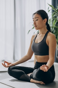 Woman practicing yoga on mat at home