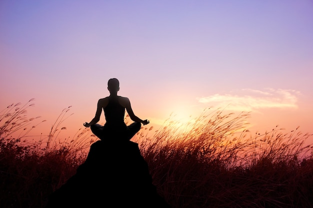 Woman practicing yoga and meditation silhouette on nature sunset background