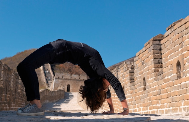 Woman practicing yoga at the mutianyu section of the great wall of china, beijing, china