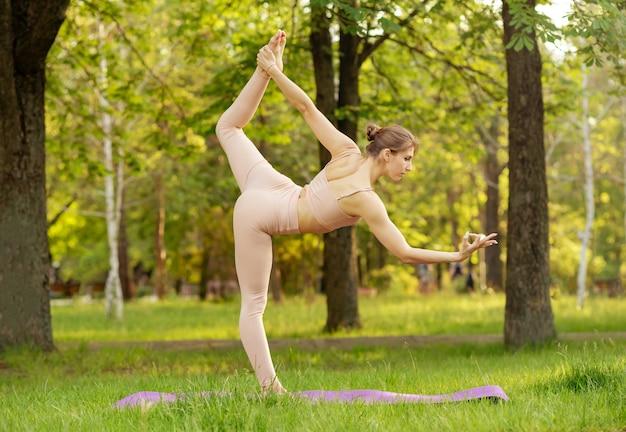 Женщина упражнениями йоги на траве в парке