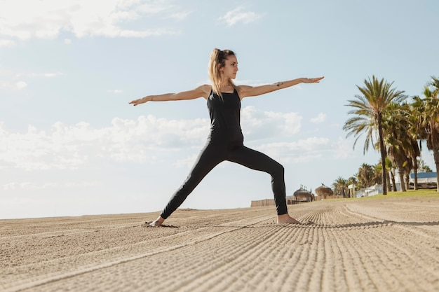 Женщина упражнениями йоги на пляже