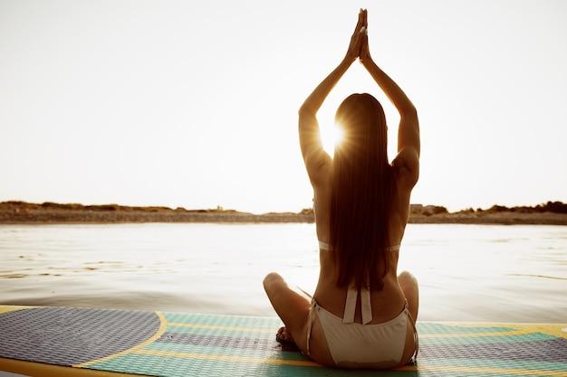 Женщина, практикующая йогу на доске с веслом по утрам