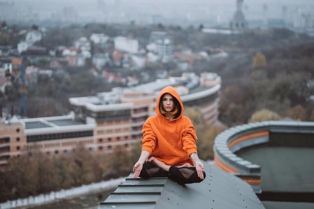 Женщина занимается йогой на крыше и делает упражнения йоги