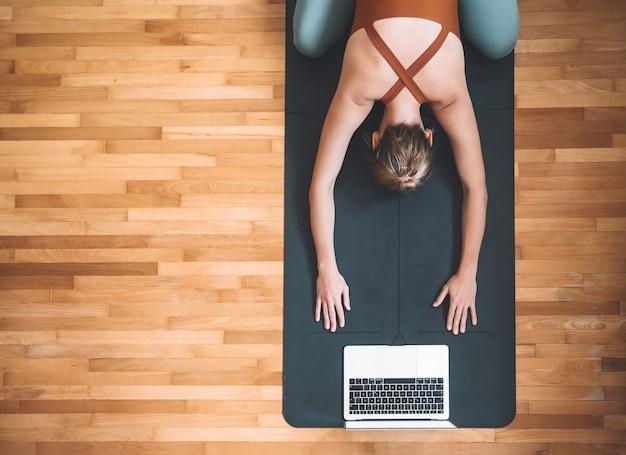 ノートパソコンでヨガマットでヨガを練習している女性オンラインスポーツクラスや瞑想の概念