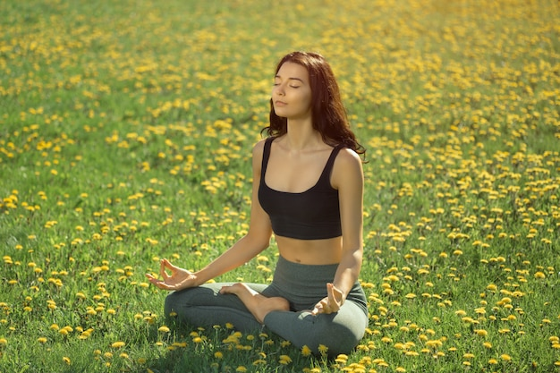 Woman practicing yoga outdoors in a park