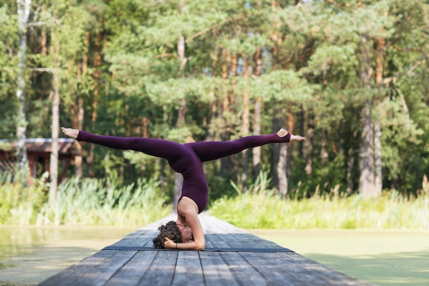 Woman practicing yoga in park performs a shirshasana exercise with a transverse twine headstand