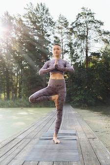 A woman practicing yoga in the park performs the vrikshasana exercise tree pose