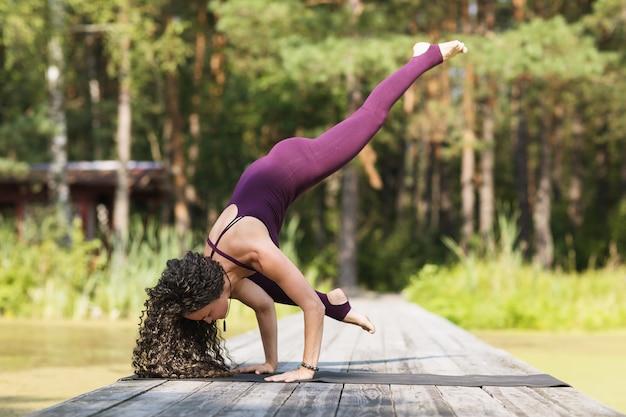 A woman practicing yoga performs the eka pada bakasana exercise crane pose