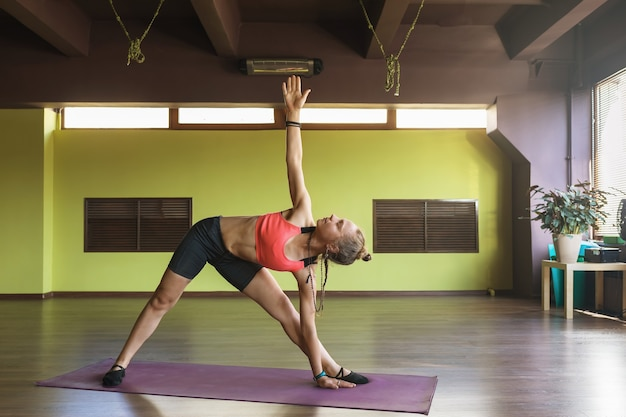 A woman practicing yoga performs the exercise utthita trikonasana the stretched triangle pose