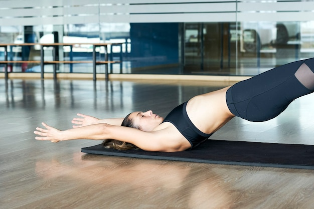 Woman practicing yoga or pilates concept in a gym, exercising in black sportswear, doing hundred pose.