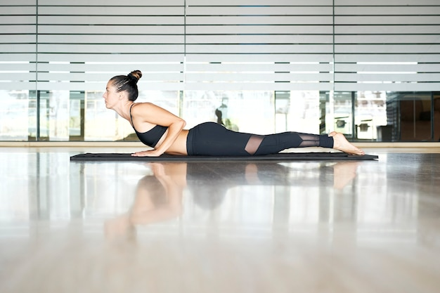 Woman practicing yoga or pilates in a gym, exercising in black sportswear, doing back extension.