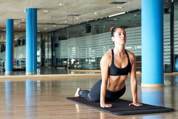 Woman practicing yoga or pilates in a gym, exercising in sportswear, doing back extension. bhujangasana