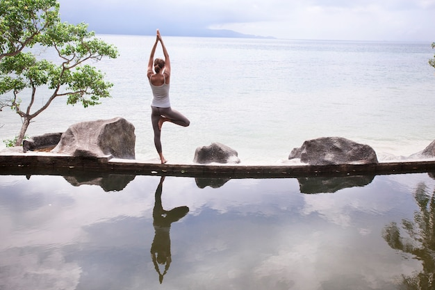 Woman practicing yoga pose in front of the lake at sunrise.