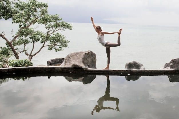 Woman practicing yoga pose in front of the lake