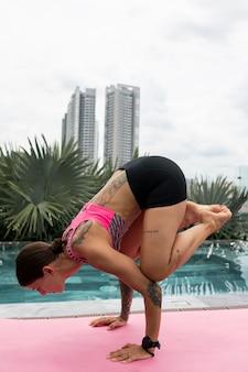 Posizione di yoga di pratica della donna in piscina
