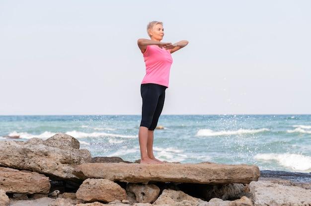 해변에서 요가 위치를 연습하는 여자. 요가와 명상 개념.