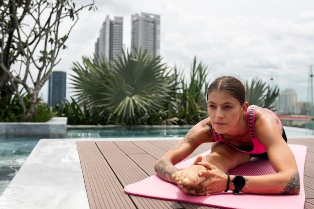 La donna a praticare yoga posizione fuori dalla piscina