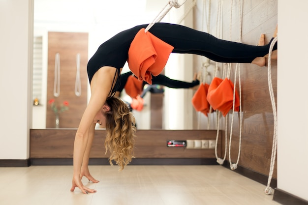 Woman practicing yoga on ropes stretching in gym. fit and wellness lifestyle