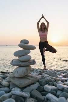 Woman practicing yoga on the seashore in the evening performs the vrikshasana exercise a tree pose