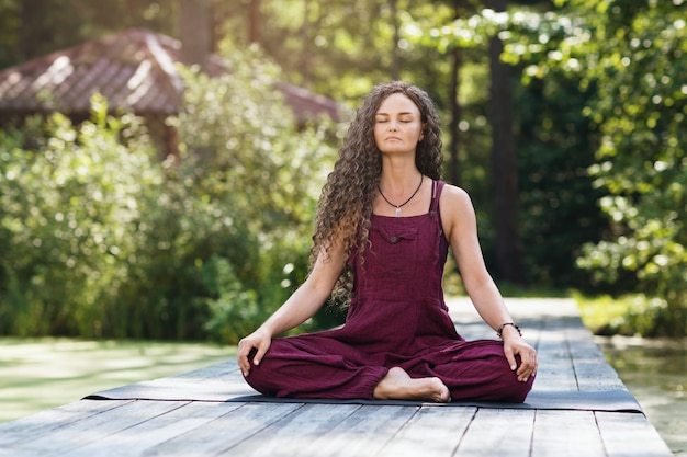 Woman practicing yoga sitting on a mat in a lotus position is engaged in meditation