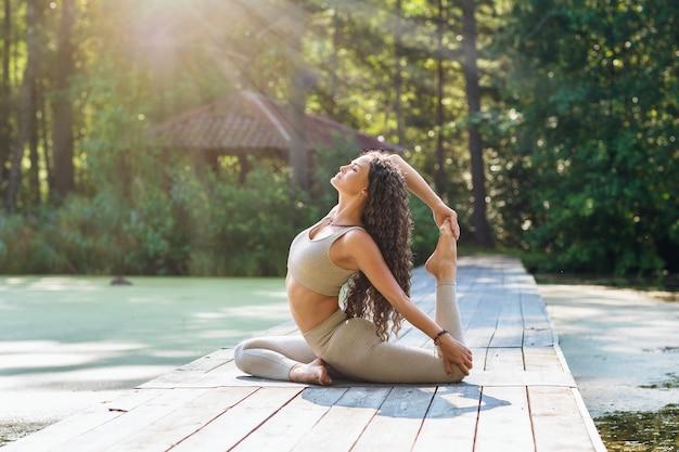 Woman practicing yoga sitting on a mat in the park doing the exercise eka pada rajakapotasana