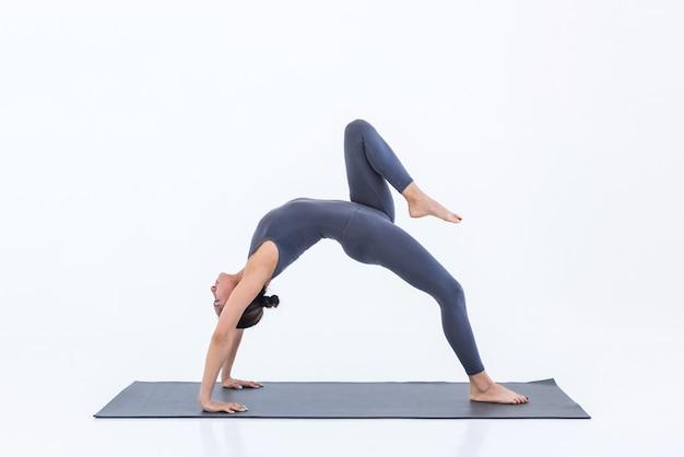 Woman practicing yoga standing in bridge pose on mat indoors