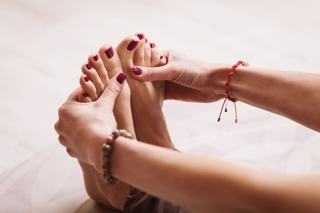 Woman practicing yoga therapy performs foot massage