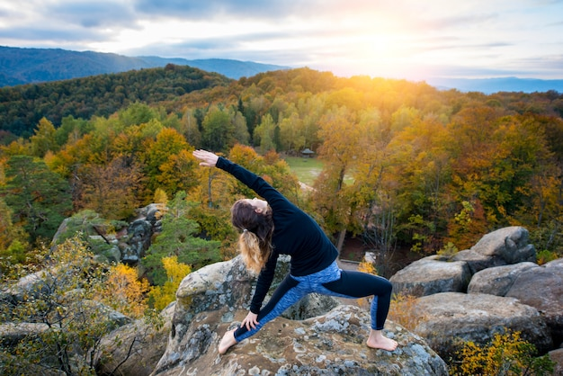 Woman practicing yoga on top of the mountain in the evening