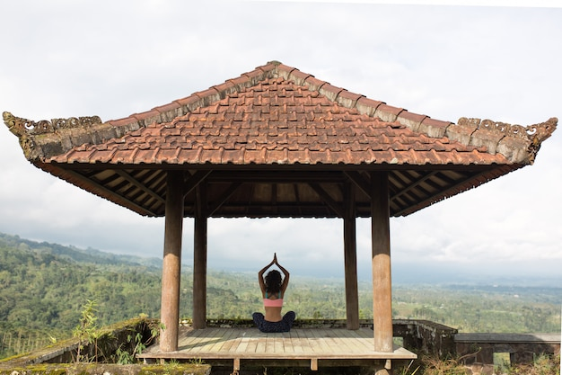 Woman practicing yoga in the traditional balinesse gazebo