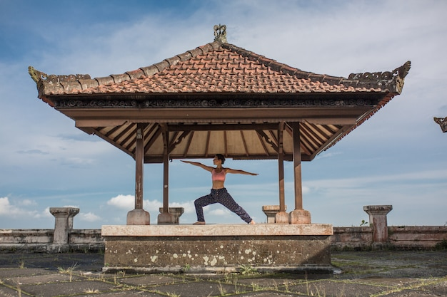 Woman practicing yoga in the traditional balinesse gazebo.